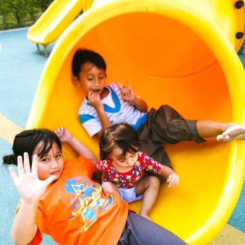 High angle view portrait of siblings sitting on slide at playground