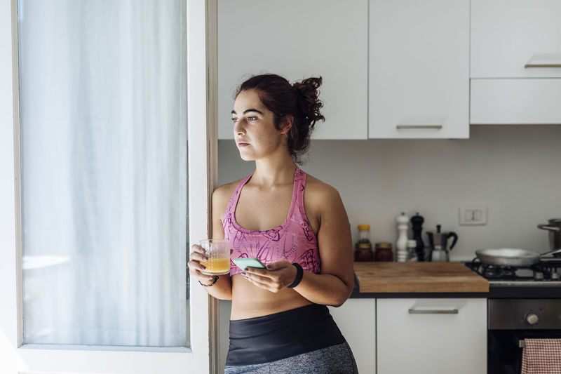 Young woman drinking glass at home