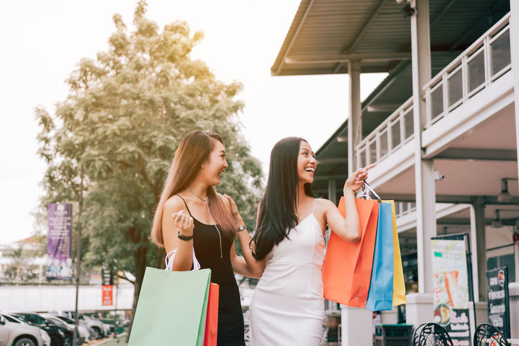 Happy friends with colorful shopping bags while standing on street in city