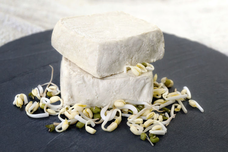 Raw tofu pieces on a stone base of the board and soybeans, the raw material from which we get the tofu. ; White Alternative Close-up Cuisine Diet; White; Food; Food Food And Drink Healthy Eating Healthy; Indoors  No People Nutritious Soy Soybean Soybean; Tofu Vegan Food Vegetarian;