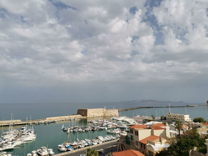 High angle view of harbor by buildings against sky