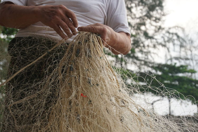 Mid Section Of A Man Holding Fishing Net