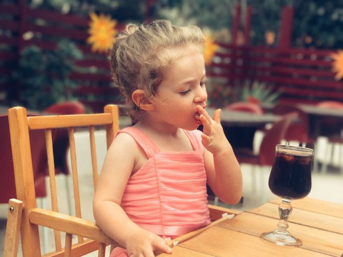 Girl looking at glass of soda while sitting on chair in restaurant