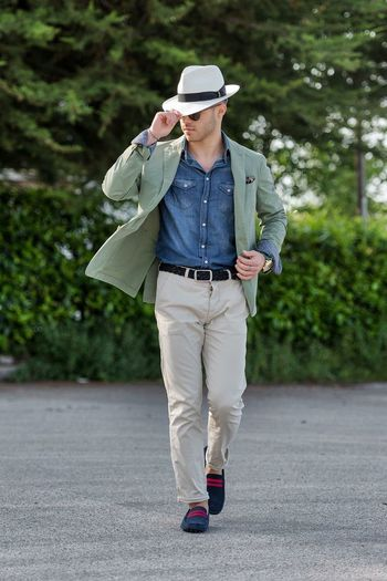 Full length of fashionable man holding hat while walking on road