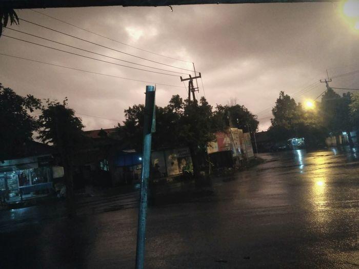 Wet street by illuminated city against sky at dusk