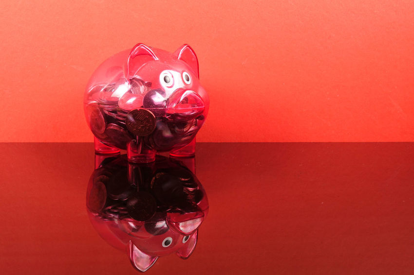 Saving concept with red piggy bank on red background. Piggy Bank Animal Representation Art And Craft Celebration Close-up Coin Colored Background Conceptual Photography  Creativity Decoration Heart Shape High Angle View Holiday Indoors  Investment No People Piggy Bank Plastic Red Representation Saving Concept Still Life Table Toy Wall - Building Feature