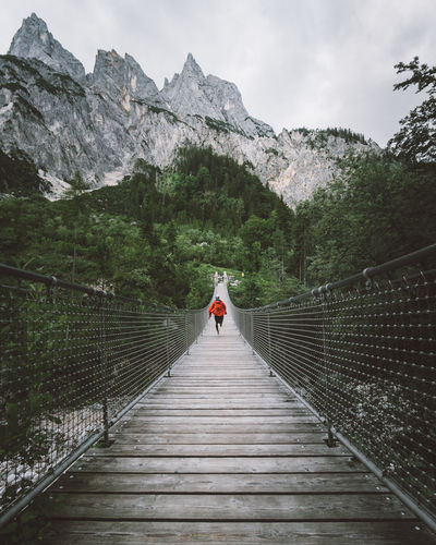 Man running on footbridge against mountains