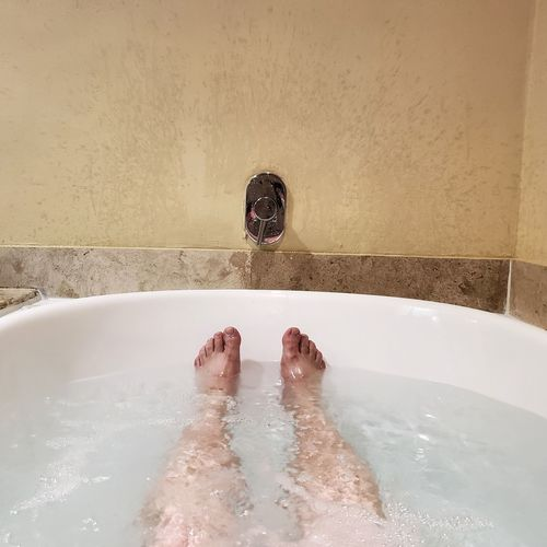 Low Section Of Person In Bathtub