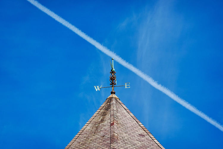 Low angle view of building against blue sky with contrail
