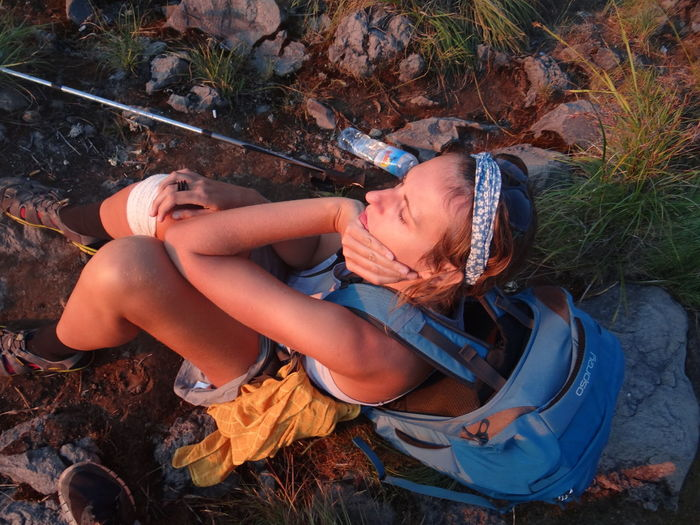 High angle view of female hiker sitting on ground