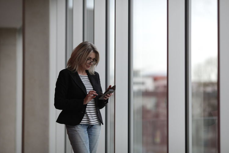 Business Woman One Person Standing Adult Three Quarter Length Wireless Technology Young Adult Indoors  Communication Technology Looking Blond Hair Women Business Person Real People Connection Hair Window Office Hairstyle Beautiful Woman