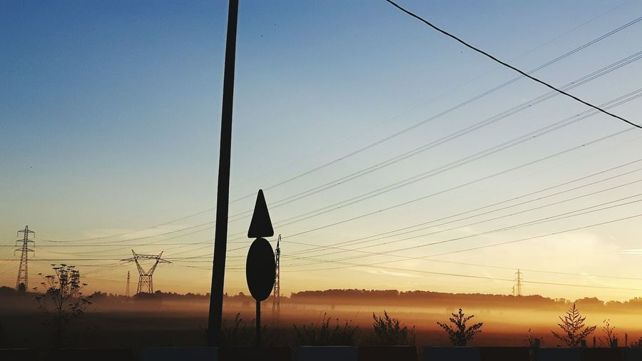 Power Line Above Landscape In Foggy Weather During Sunrise