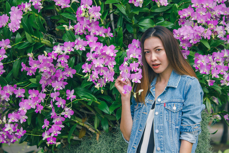 Portrait of beautiful young woman standing by purple flowering plants
