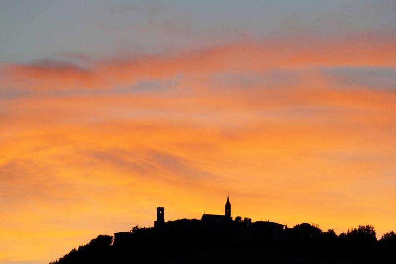 Silhouette of buildings against orange sky