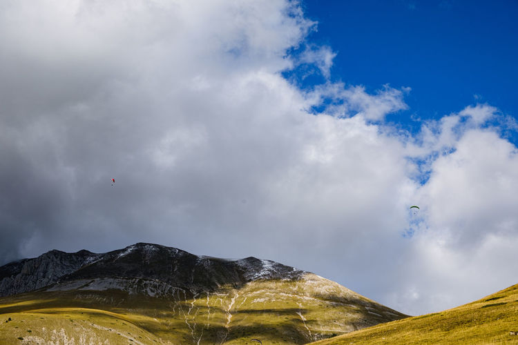 Low angle view of mountain against sky with paragliders in castelluccio, umbria italy