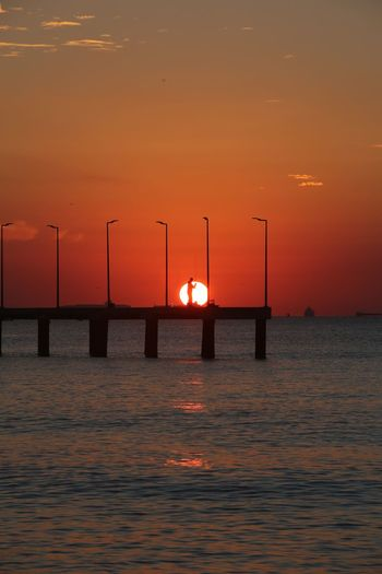 Sunset and fisherman Water Sunset Sea Sky Orange Color Beauty In Nature Scenics - Nature Tranquility Idyllic Tranquil Scene Waterfront Nature No People Horizon Over Water Built Structure Transportation Horizon Architecture Outdoors
