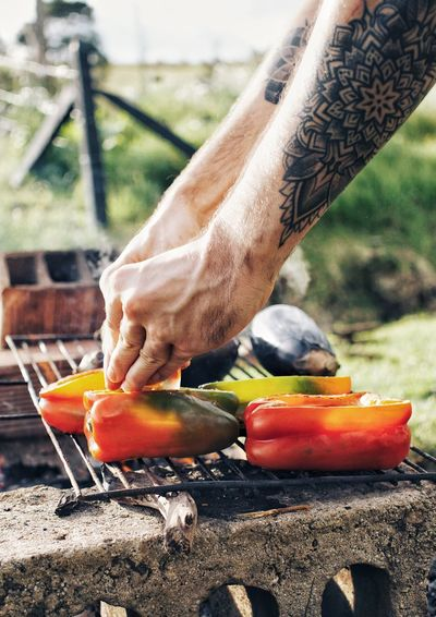 Cropped hands of man preparing bell peppers on barbecue grill