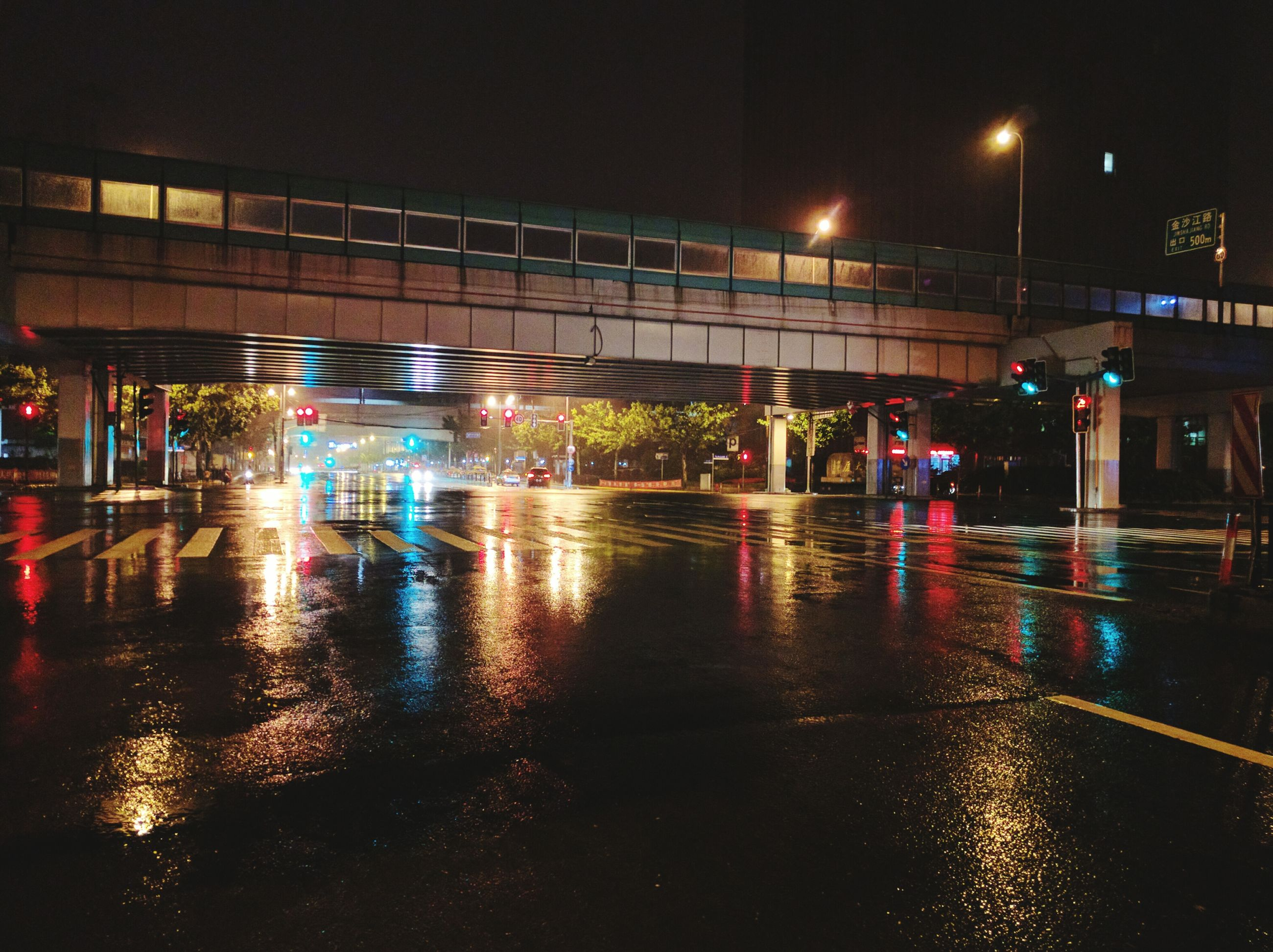 illuminated, night, transportation, built structure, architecture, city, building exterior, street, reflection, wet, street light, lighting equipment, city life, road, mode of transport, motion, long exposure, water, rain, blurred motion