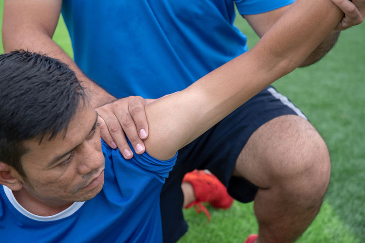 Low Section Of Male Physical Therapist Stretching Soccer Player Hand On Field