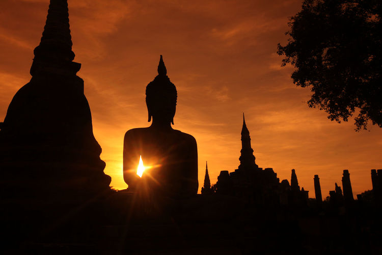 Silhouette statue of temple at sunset