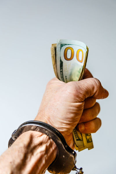 Handcuffed by a love for money. Arrest Close-up Currency Hand Hand Clinched Handcuffs  Human Hand Love Of Money Money Paper Currency White Background