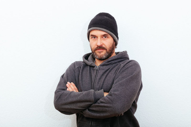 Mature man in best age with beard and cotton hat, standing confident on wall, looking towards camera. 40 Arms Best Ager Casual Clothing Caucasian Confidence  Contemplation Crossed Fashion Front View Mature Person Portrait Real People Standing Waist Up