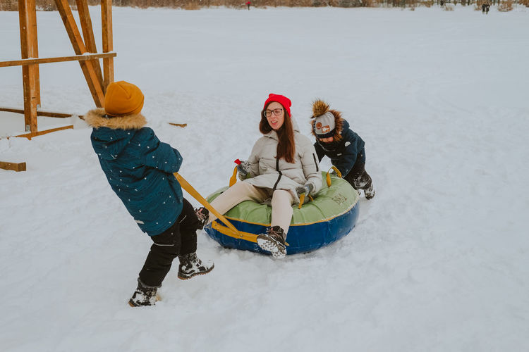 Children ride a tubing. mom and children ride a tubing. outdoor winter games for the whole family.