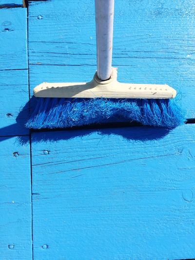 High angle view of broom on blue porch during sunny day