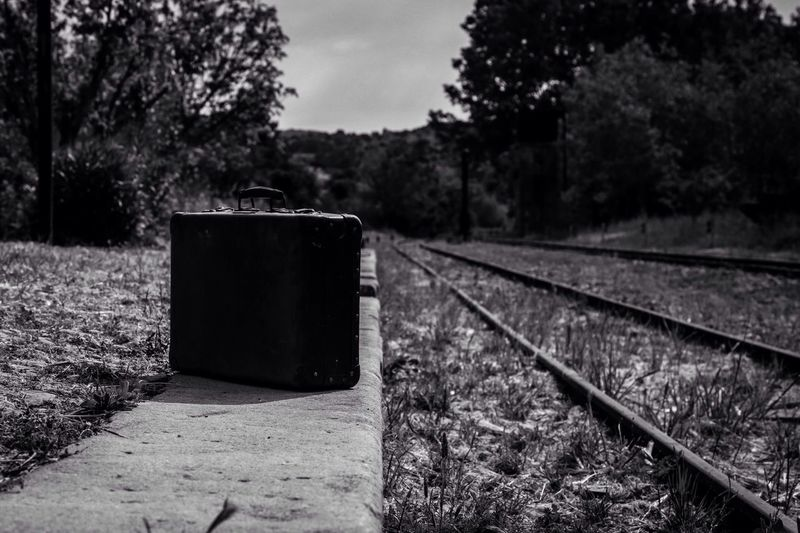 Briefcase by railroad tracks