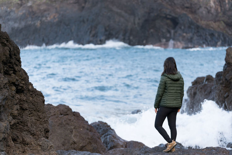 Woman seeing waves crashing on a rocky beach at Seixal, Madeira Madeira Seixal Portugal Landscape Nature Seascape Ocean Atlantic Sea Rocks Travel Outdoors Panorama Panoramic View Rock Waves Girl Woman Traveler Power Alone Loneliness Beach Crashing