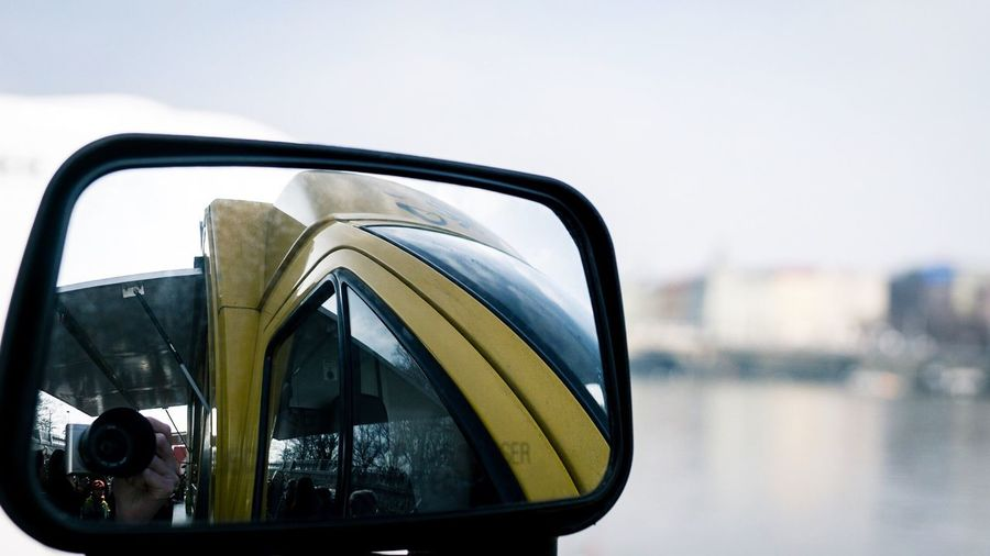 Reflection of bus in side-view mirror against sky