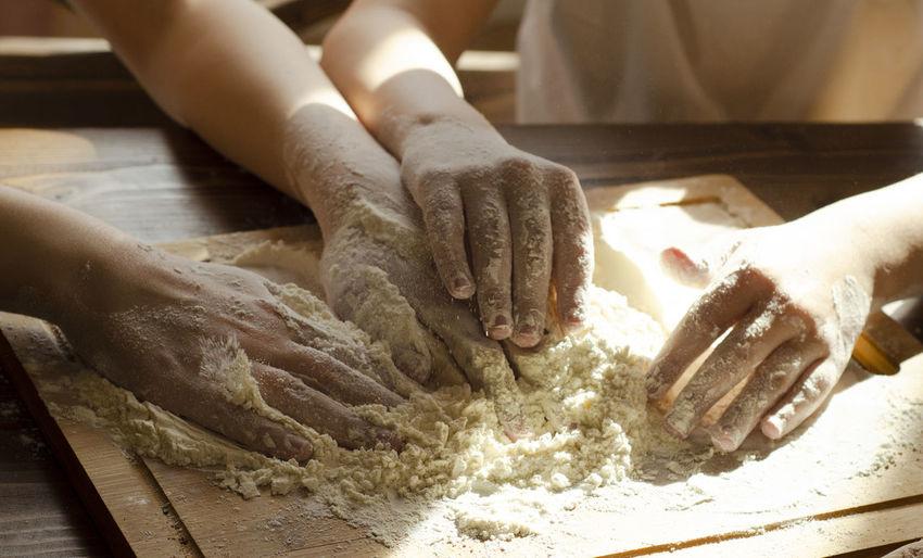 Children's hands preparing food with a flour