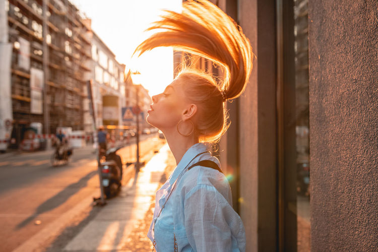 Side view of young woman tossing hair while standing on sidewalk during sunset