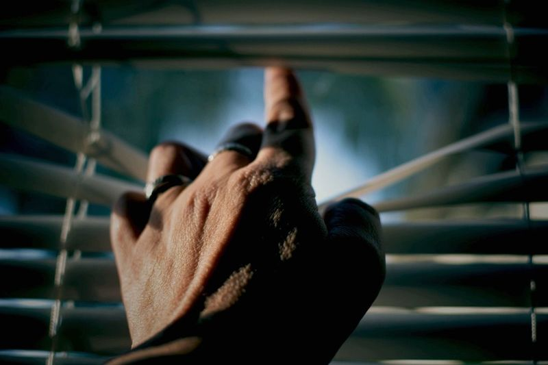 Close-up of human hand next to window