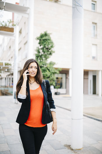 Young businesswoman using the smartphone when leaving work Worker Architecture Beautiful Woman Business Activity Businesswoman Day Finishedwork Happiness Lifestyles Mobile One Person Outdoors Portrait Real People Smartphone Smiling Technology Using Phone Young Adult Young Women