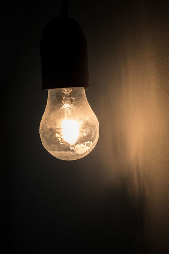 Old vintage light bulb glowing in the dark. Ideal for concepts. Background Beautiful Black Bright Bulb Ceiling Cold Dark Darkness DIM Dusty Electric Electricity  Filament Glass Glow Glowing Grunge Hanging Idea Illuminate Illuminated Incandescent Interior Isolated Isolation Lamp Light Lightbulb Old Power Retro Shine Shiny Vertical Vintage Wall Yellow