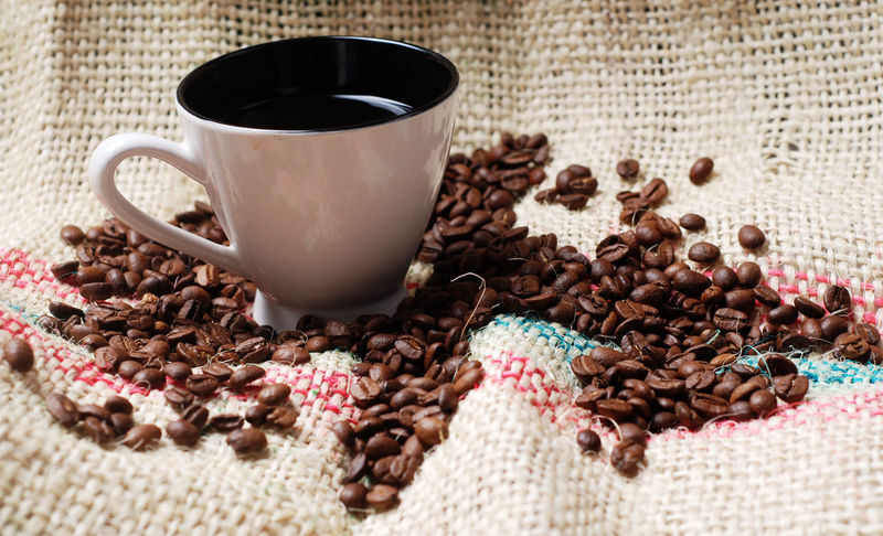 Cup of coffee with coffee beans on the hessian Brown Close-up Coffee Beans Coffee Cup Cup Day Dried Fruit Drink Food And Drink Freshness Healthy Eating Hessian Indoors  No People Refreshment