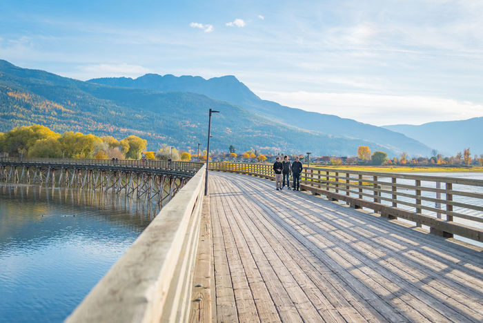 Salmon Arm, British Columbia/Canada - October 22, 2016: families take an evening walk along the longest curved pier in North America, located at the Salmon Arm Wharf on Shuswap Lake. Autumn Autumn colors Beautiful British Columbia, Canada Families October Pier Salmon Arm Pier Salmon Arm, BC Scenic Shuswap Lake Travel View Blue Sky Curved Pier Editorial  Evening Landscape Mountains Outdoors People Sunset Tourism Walking Pier Water