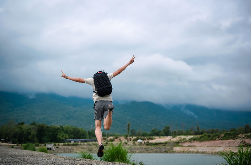 Back view point of young man backpacker jumping over the ground and raising arm with victory sign
