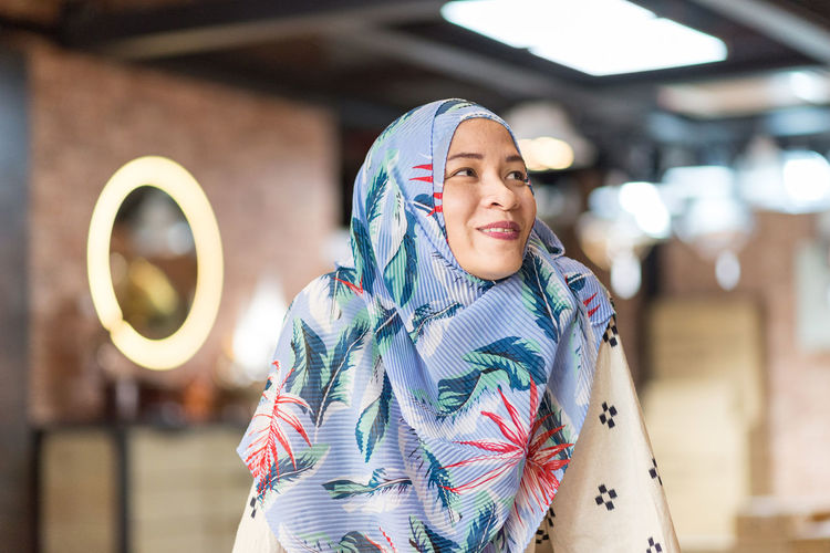 Smiling woman in hijab looking away at cafe