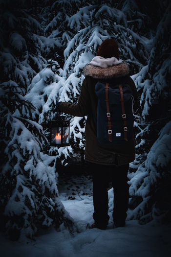Person carrying lantern and backpack in winterly forest