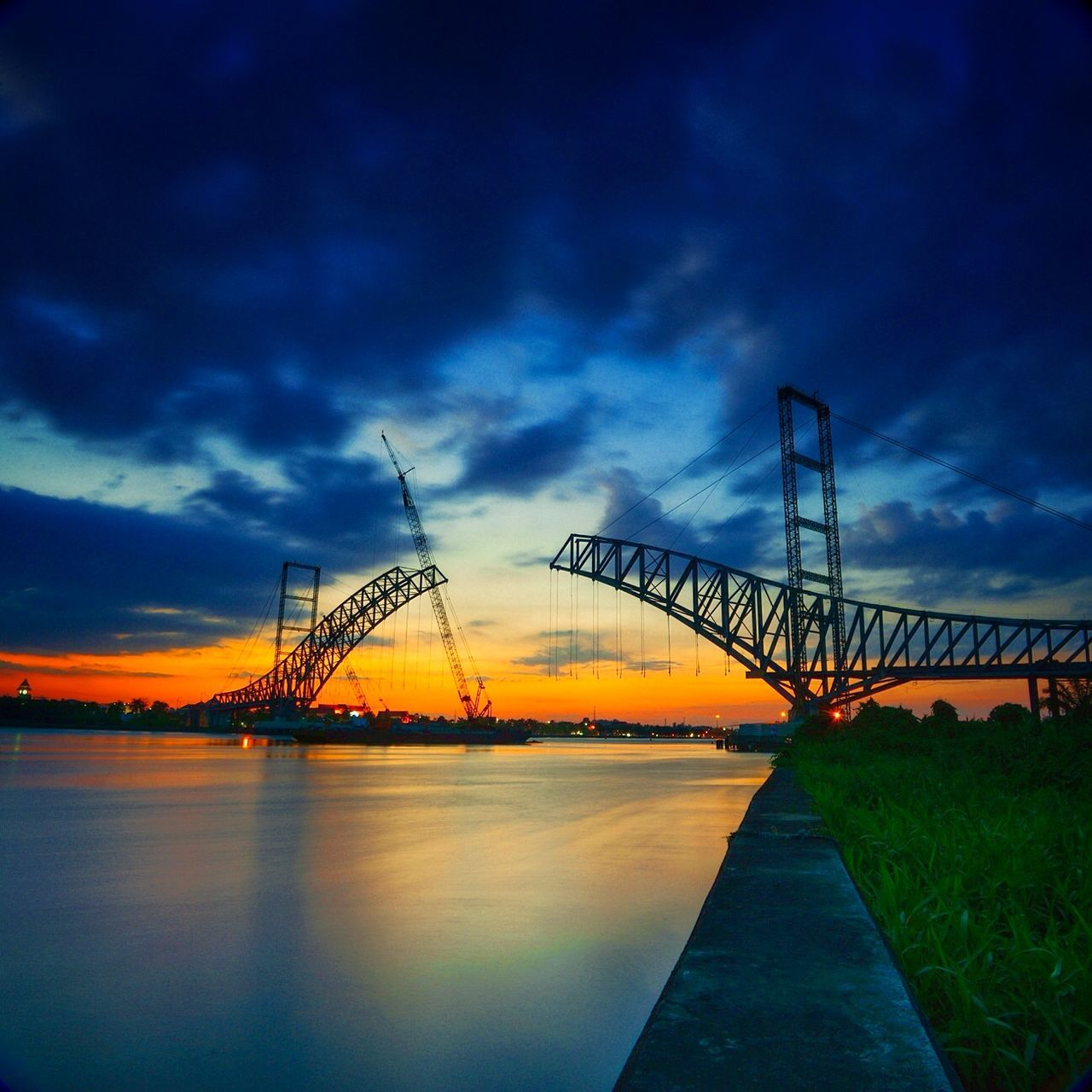 sky, bridge - man made structure, built structure, connection, cloud - sky, architecture, outdoors, sunset, water, travel destinations, no people, nature, transportation, building exterior, beauty in nature, industry, city, day
