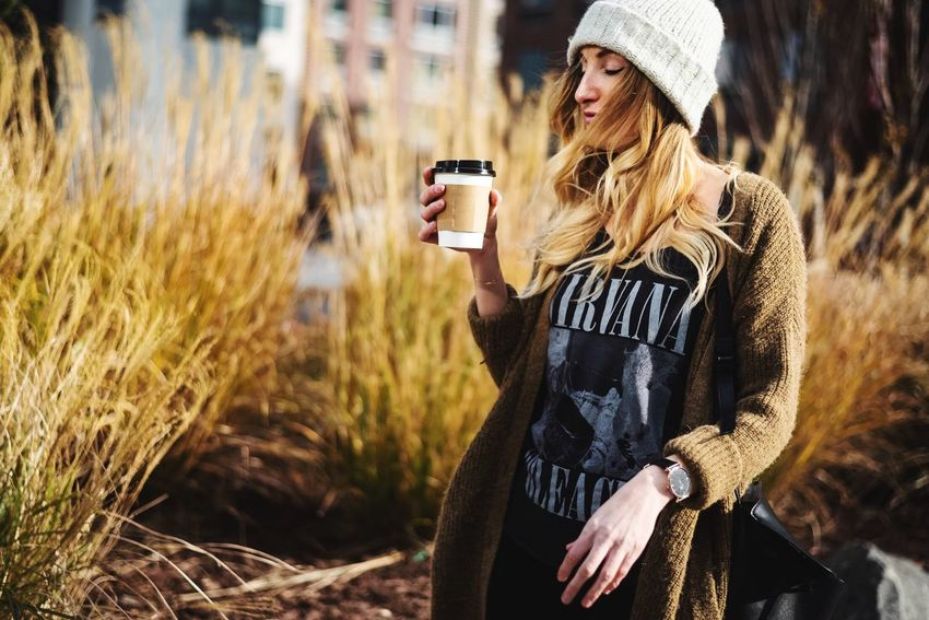 Clothing Lifestyles Leisure Activity One Person Holding Real People Technology Young Adult Wireless Technology Nature Land Drink Refreshment Sunlight Smart Phone Plant Field Mobile Phone Adult Warm Clothing