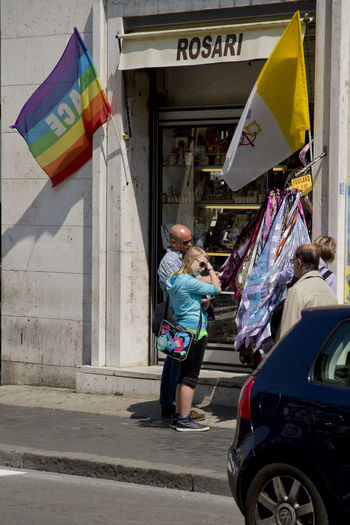 Shop Casual Clothing City City Life City Street Contrast Contrasts Day Flags Full Length Gay Pride Leisure Activity Lifestyles Outdoors Rainbow Flag Road Store Vatican Vatican City Vatican Flag TakeoverContrast Flag GAY FLAG Rainbow Gay Pride Flag Two People