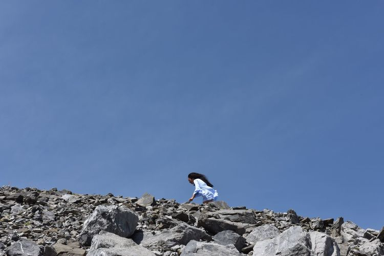 Low angle view of woman standing on rock formation against clear blue sky