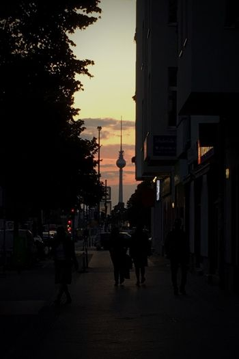 Silhouette of people walking on road at sunset
