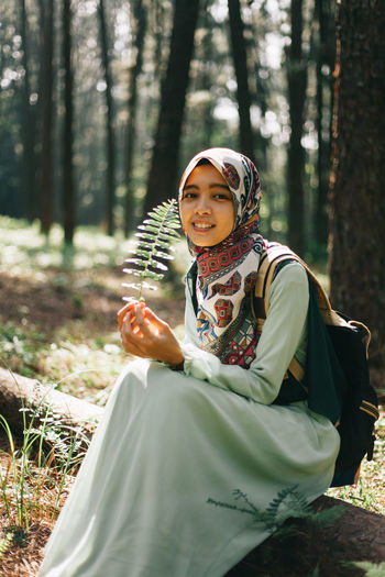 Portrait of smiling young woman sitting on tree trunk in forest