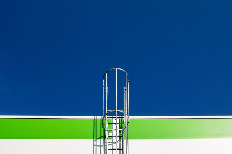 Ladder against on wall clear blue sky