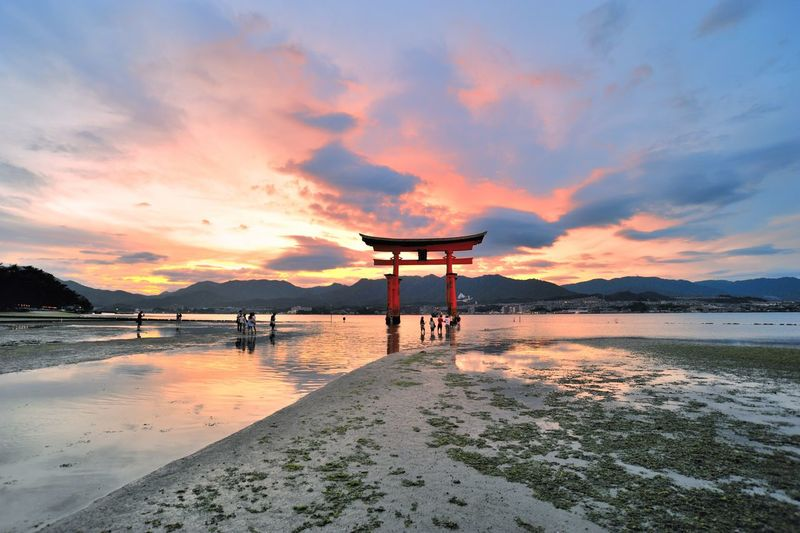 Torii Gate In Sea At Itsukushima Shrine Against Sky During Sunset