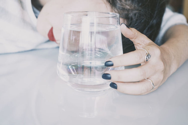 Midsection of person holding glass of water